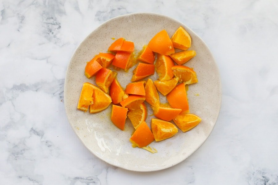 Cooked oranges cut into pieces on a plate.