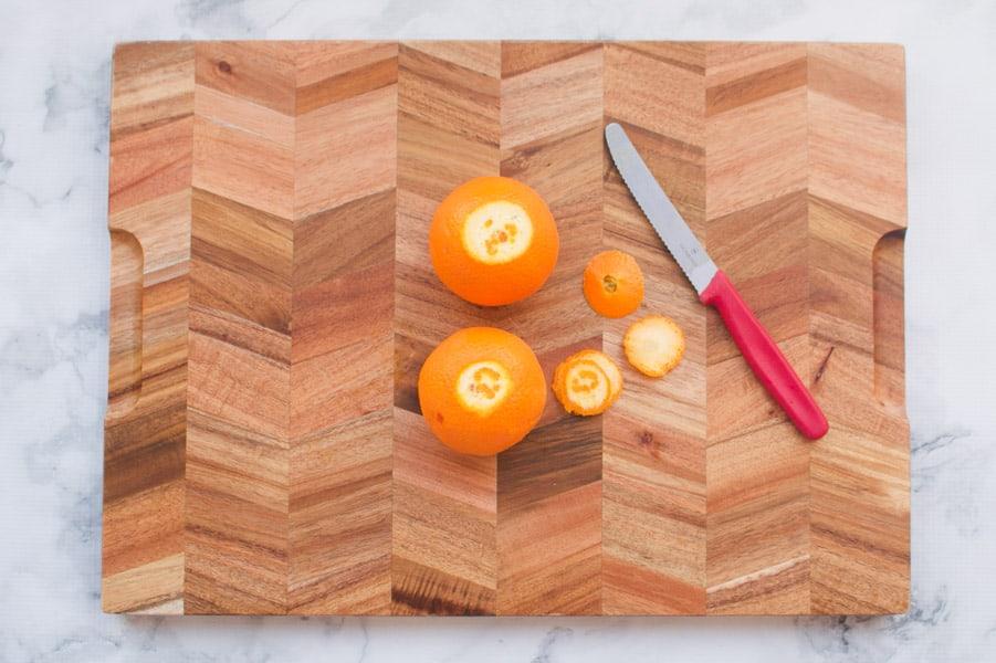 Oranges being cut on a chopping board.