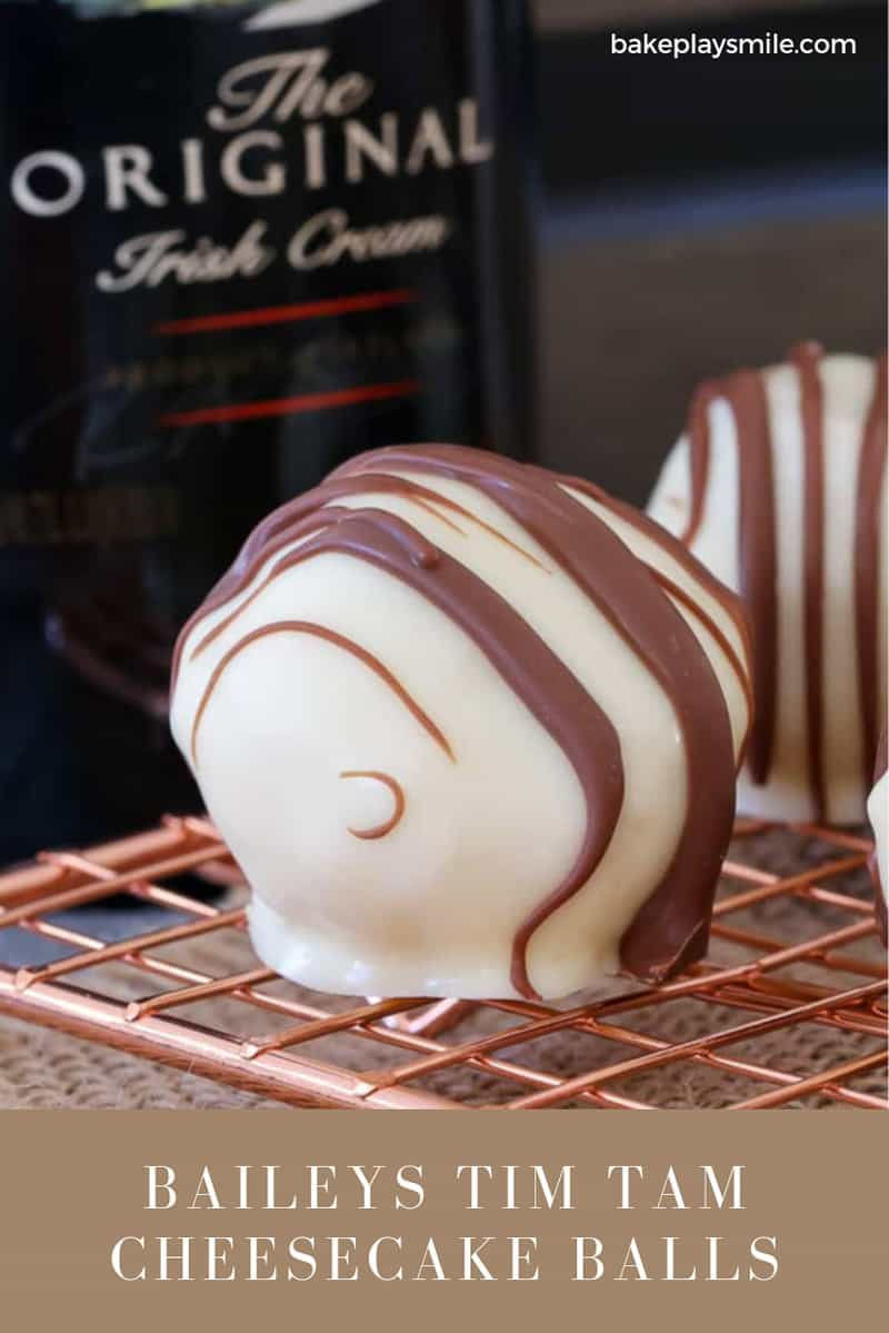 A truffle covered in white chocolate and drizzled with milk chocolate.