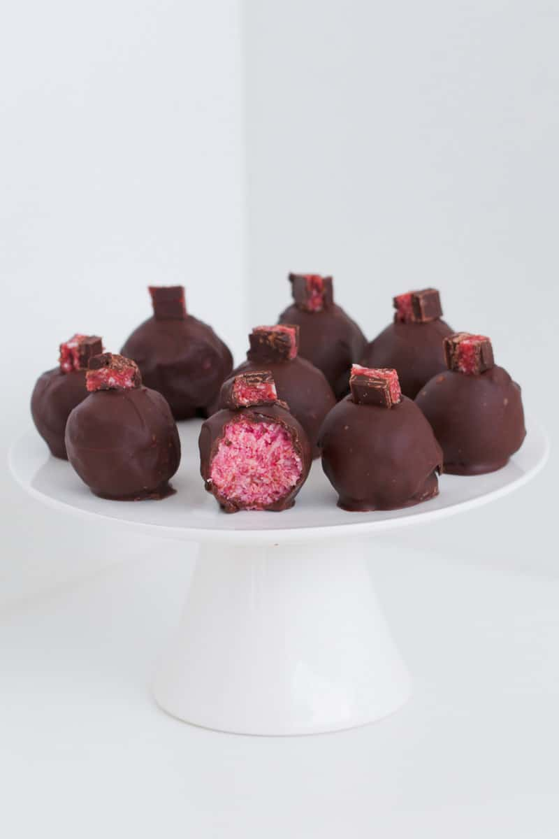 A plate of dark chocolate, coconut and cherry balls.