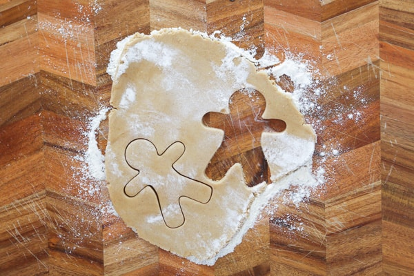 Gingerbread men shapes being cut out from dough on a chopping board.