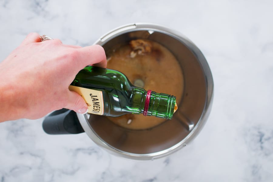 Pouring whiskey into a Thermomix to blend homemade Baileys