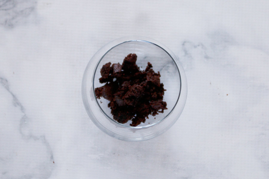 Crumbled brownie in the base of a glass jar.