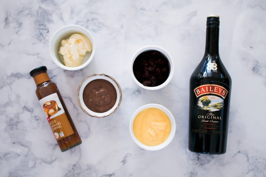 All the ingredients for a trifle made with Baileys, brownie, custard, whipped cream and salted caramel sauce.