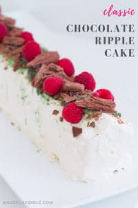 A whipped cream chocolate ripple cake decorated with peppermint crisp, raspberries and chocolate.