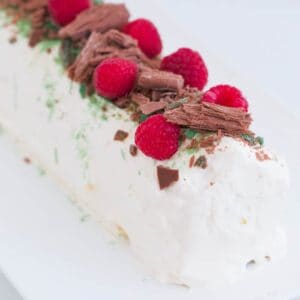A whipped cream chocolate ripple cake decorated with raspberries, Peppermint Crisp and chocolate.