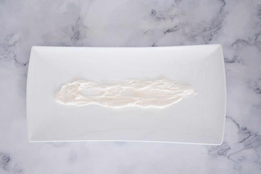 Whipped cream spread along a white rectangular serving dish.
