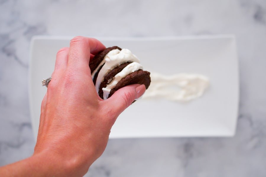 Chocolate biscuits being sandwiched together with whipped cream.
