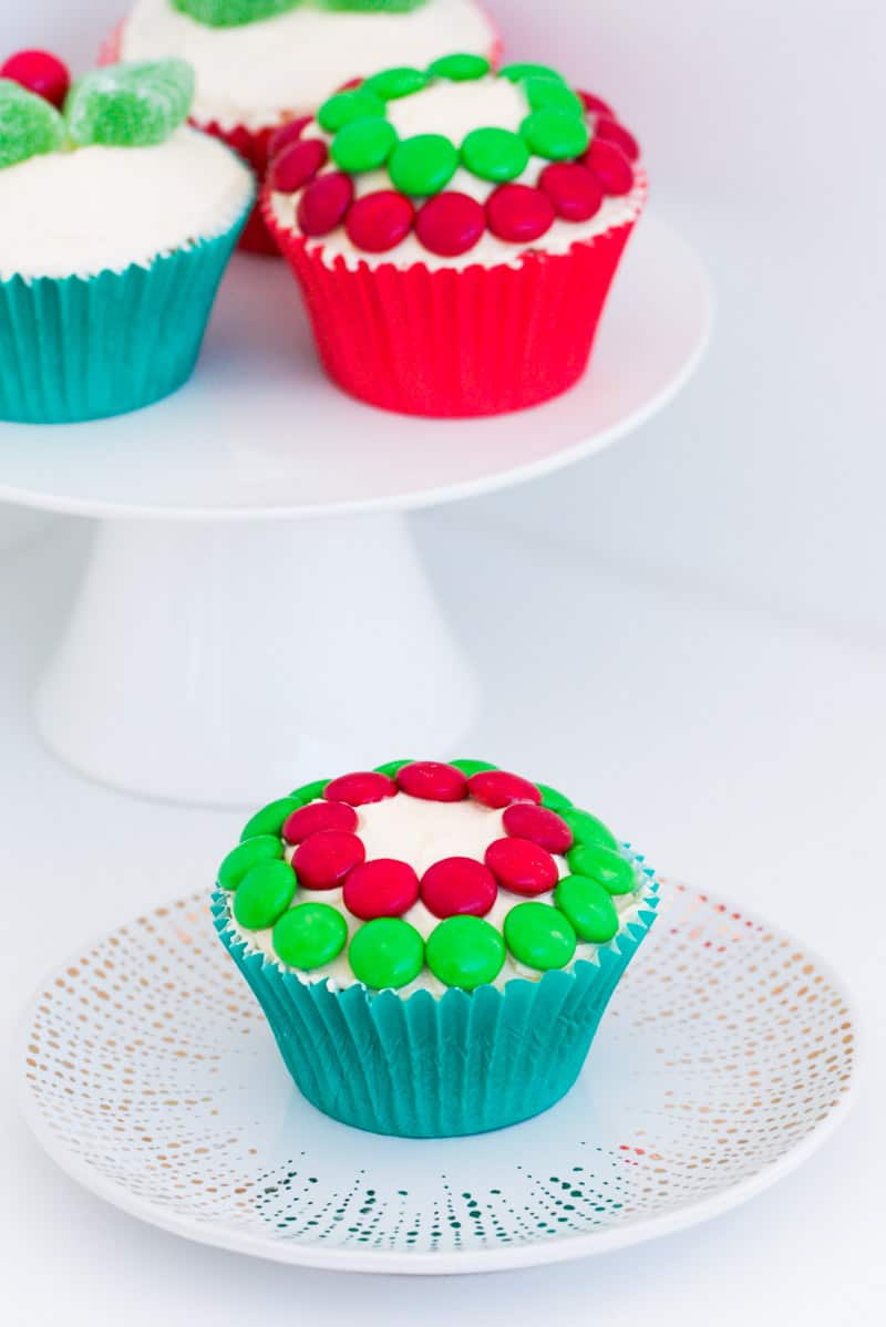 Red and green Christmas cupcakes on a cake stand with another in front.
