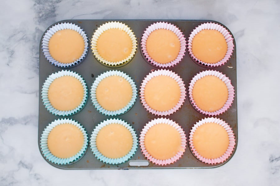Vanilla cupcake mixture in a muffin tray.