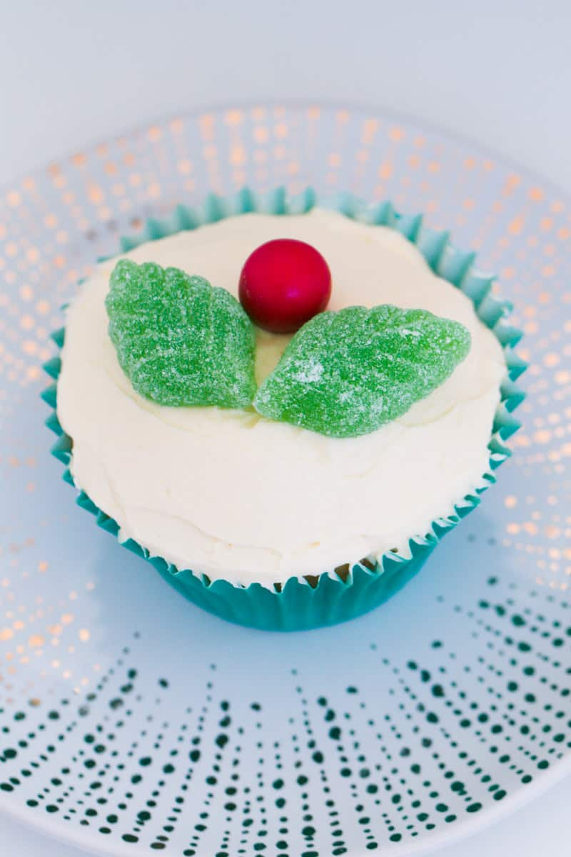 A Christmas cupcake decorated with buttercream, spearmint leaves and a red chocolate.