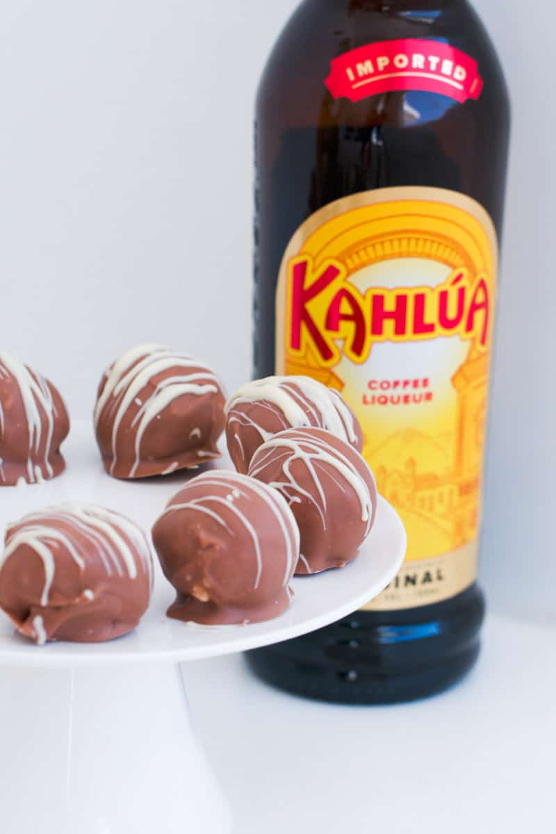 Chocolate coated Kahlua cheesecake balls on a white cake stand.