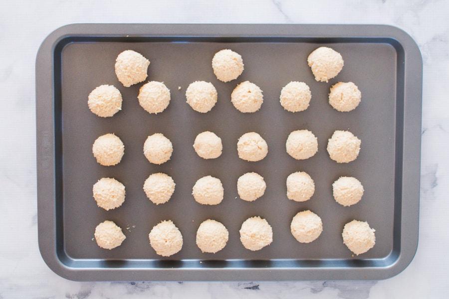 White chocolate cheesecake ball mixture on flat baking trays.