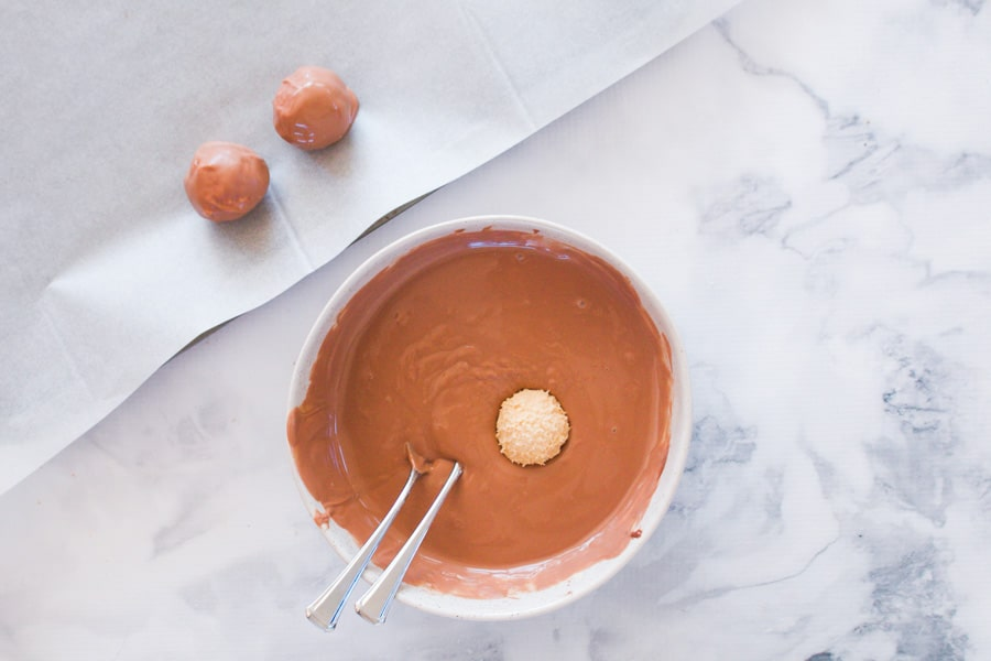 A Kahlua cheesecake ball dipped into a bowl of melted chocolate.