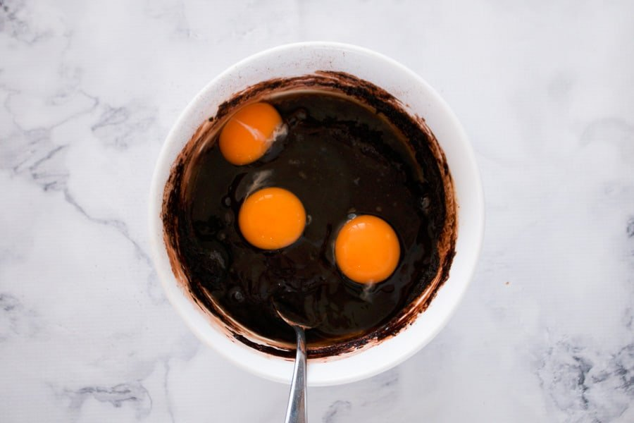 Eggs being added to a chocolate batter mixture in a bowl.