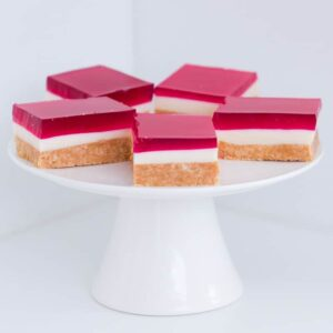 A white cake tray with five pieces of pink jelly slice