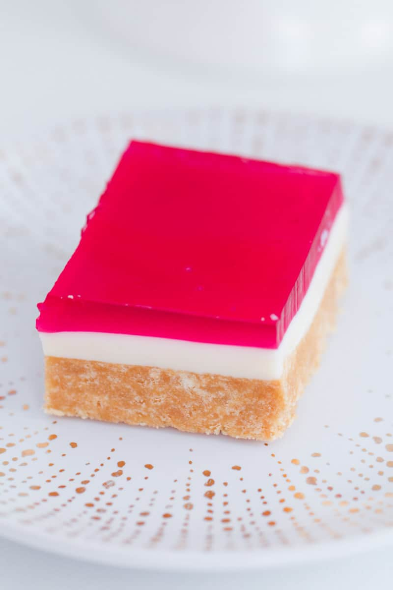 A piece of slice with three layers of biscuits, condensed milk and jelly.