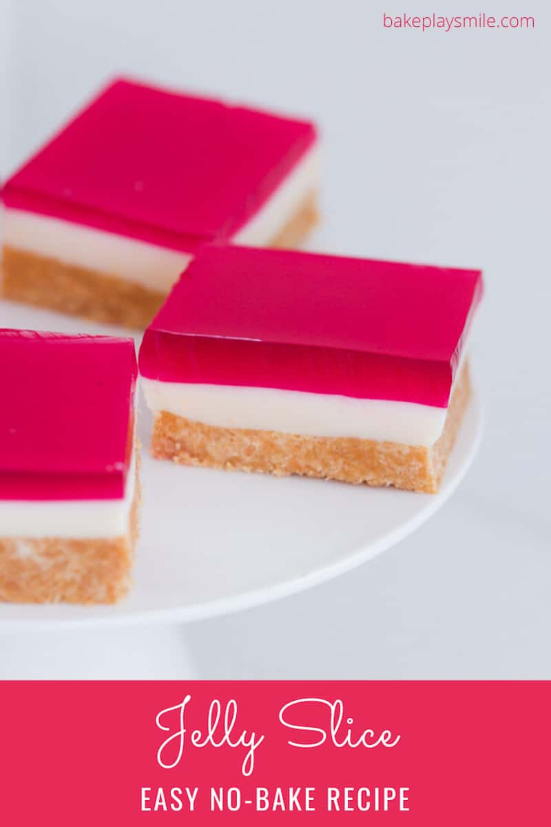 Pieces of raspberry jelly slice on a white cake stand.