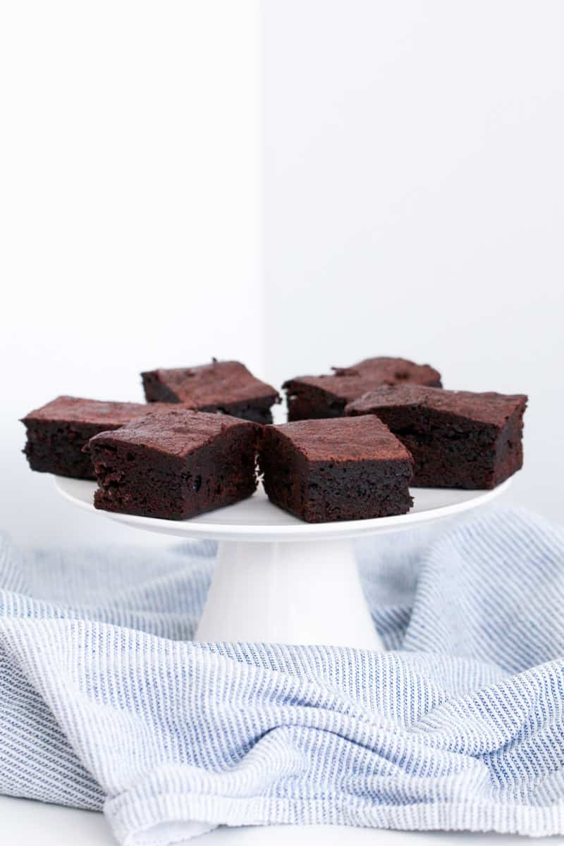 Pieces of dense chocolate brownies on a cake stand.