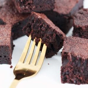 Rich and dense chocolate brownies on a gold fork.