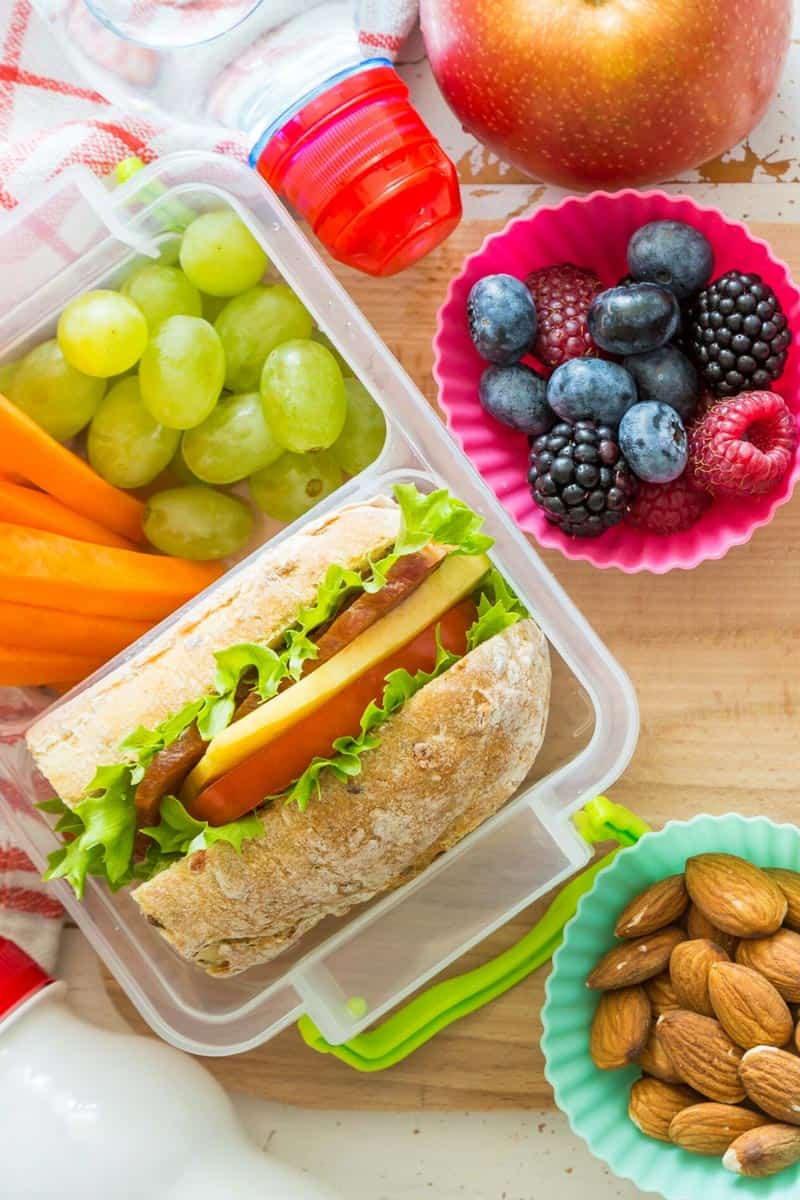 A healthy school lunchbox with fruit, a bread roll and nuts.
