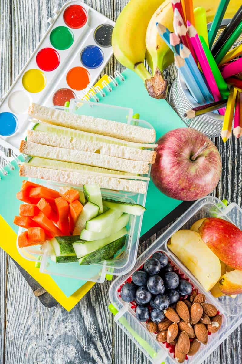 A lunch box with a healthy sandwich, fruit, nuts and vegetable sticks.