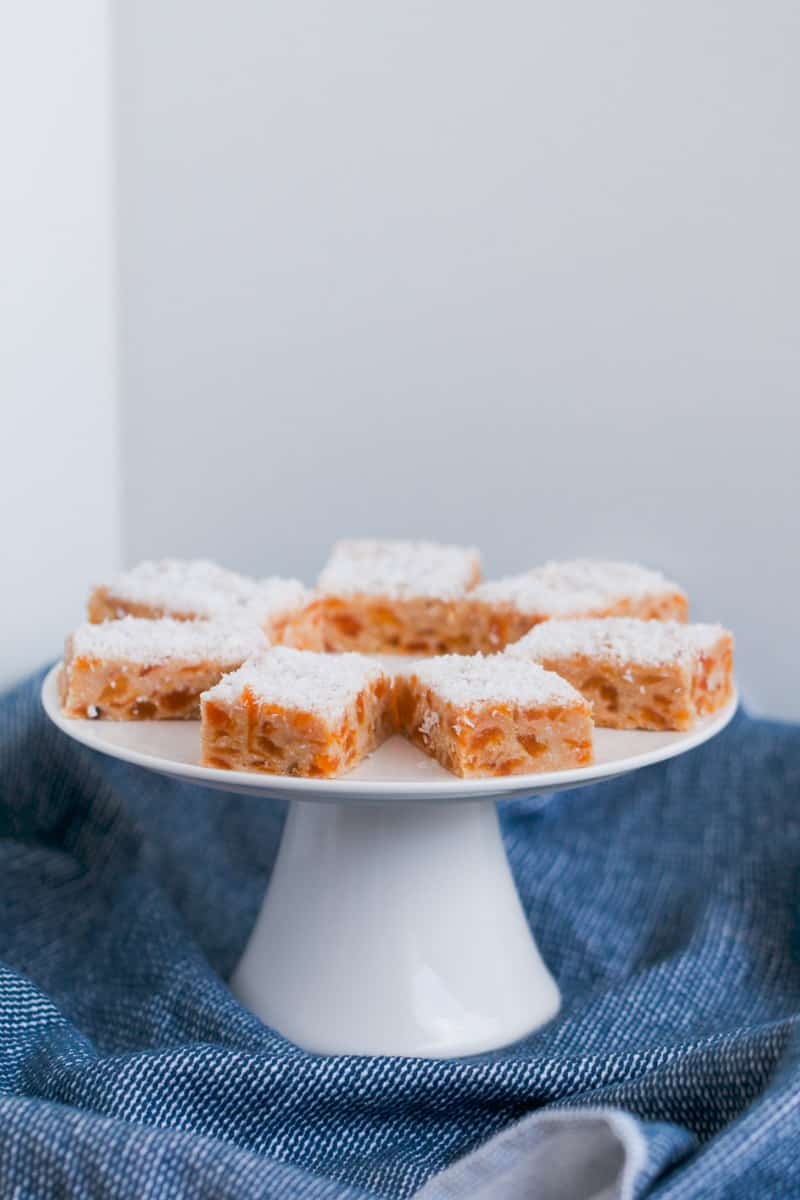 A white plate of coconut slice with chunks of apricot.