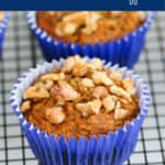 A carrot muffin topped with walnuts on a wire rack.