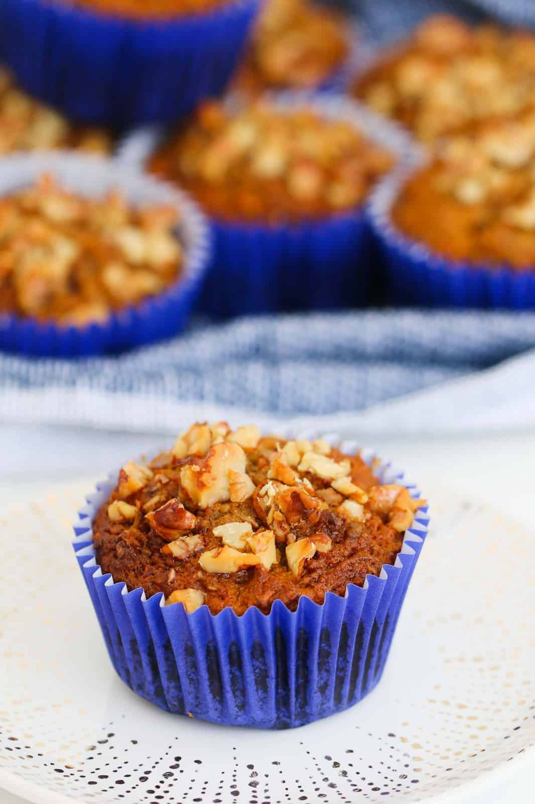 A carrot muffin with nuts on top.