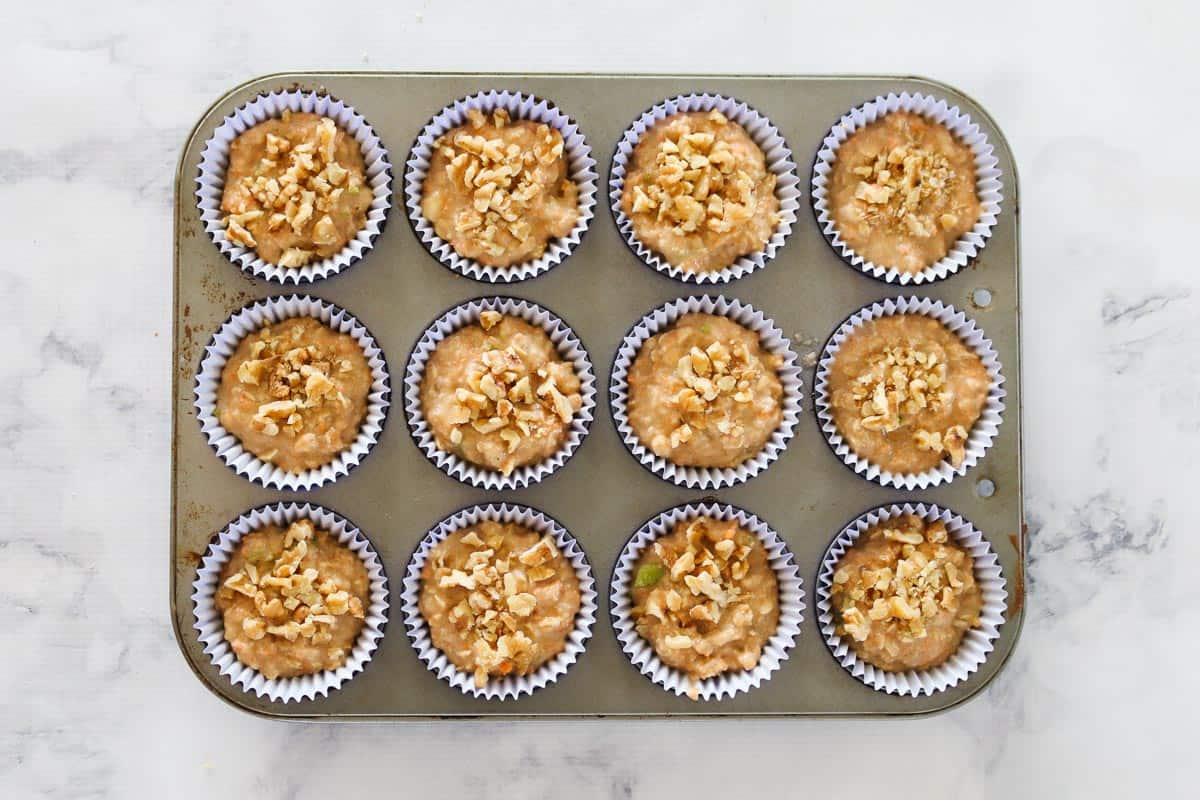 Muffin mixture in muffin with topped with walnuts.