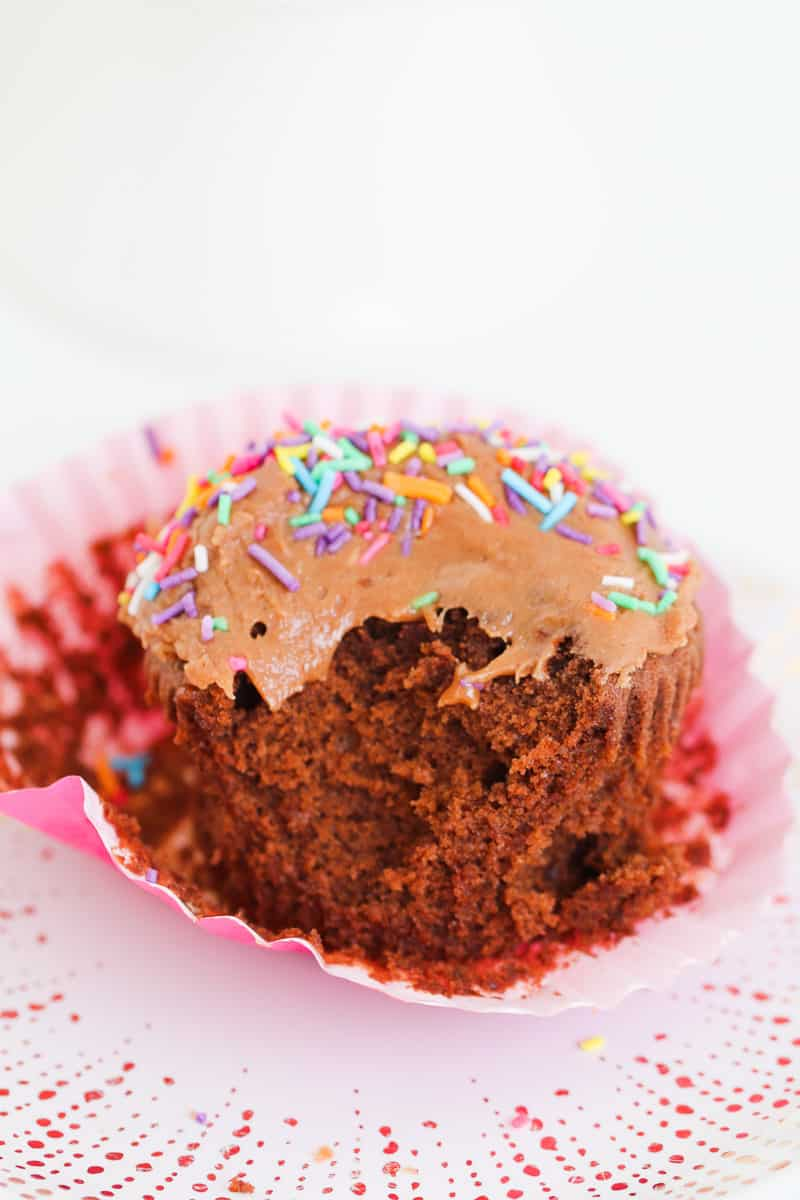A half-eaten moist chocolate cupcake with icing.