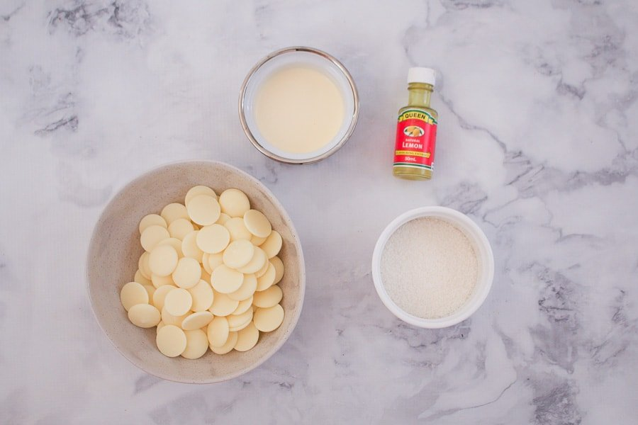 The ingredients for lemon truffles - white chocolate, lemon extract, cream and coconut.