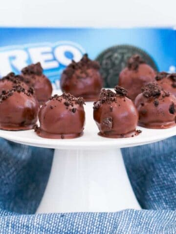 A cake tray of chocolate coated truffles, decorated with chocolate, in front of a packet of Oreo's