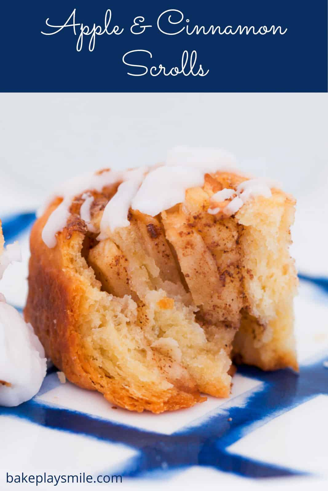 A homemade cinnamon scroll with chunks of apple and an icing sugar glaze.