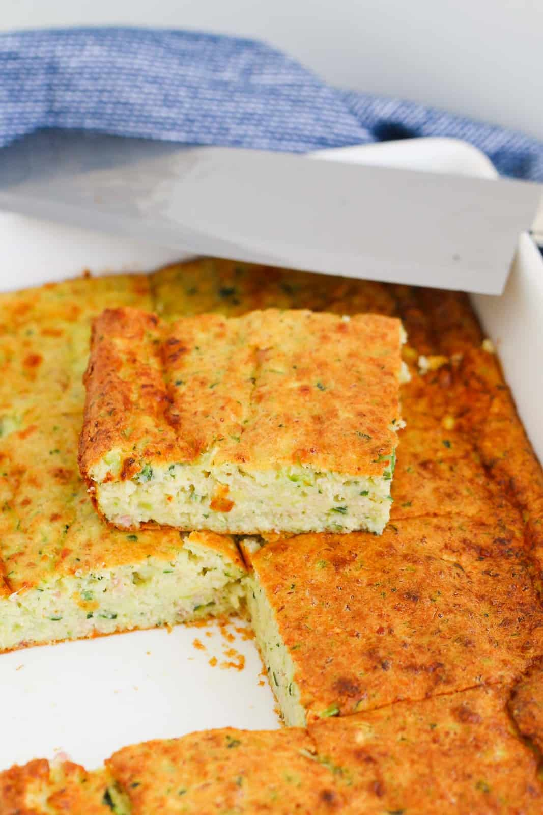 One slice of zucchini and bacon slice taken out of a white baking tray.