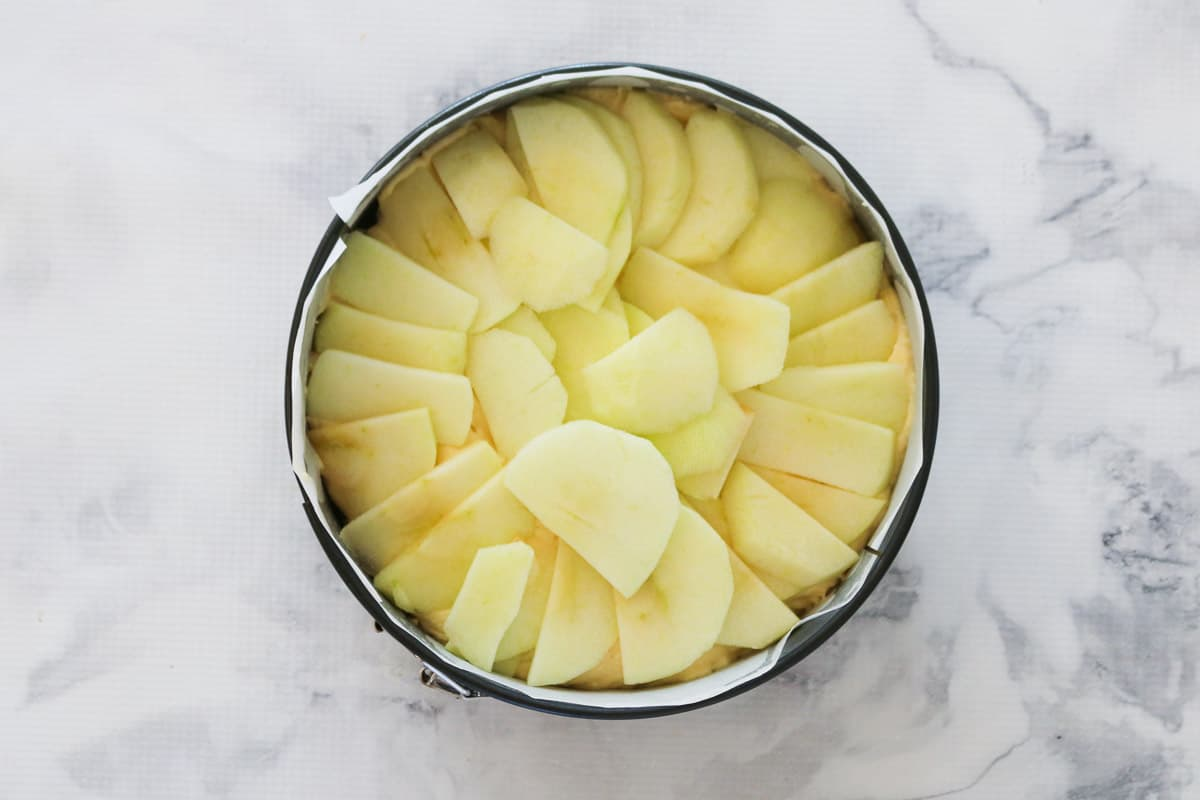 Apple slices on top of a butter cake mixture in a cake tin.