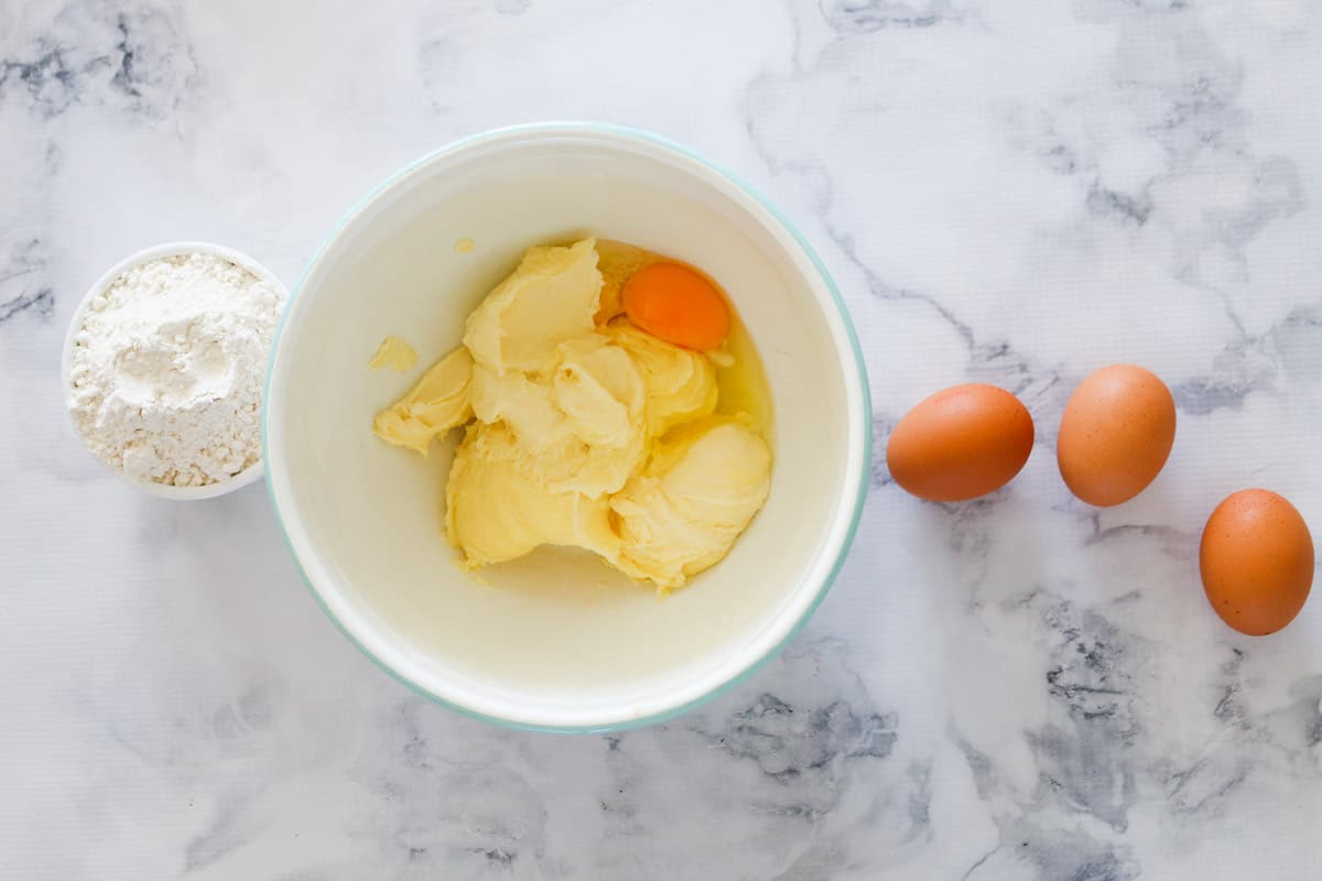 Creamed butter and sugar with eggs in a mixing bowl.