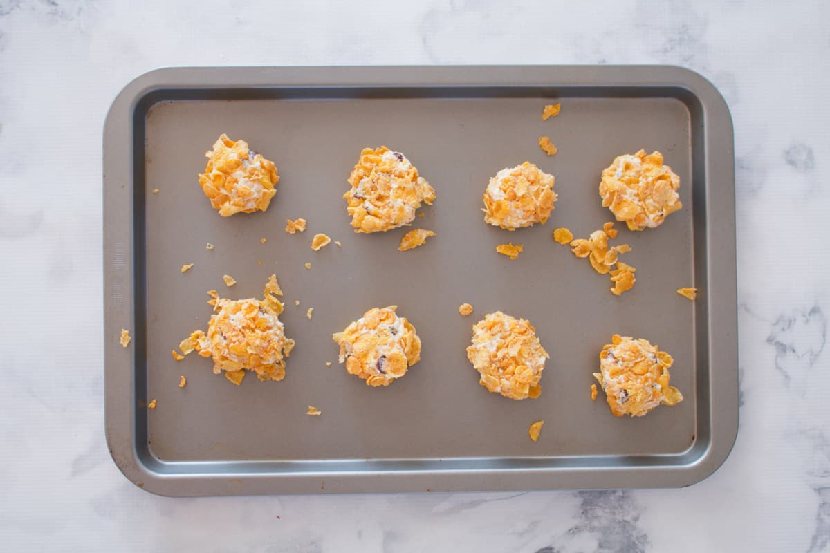 Cookies rolled in cornflakes on a baking tray.
