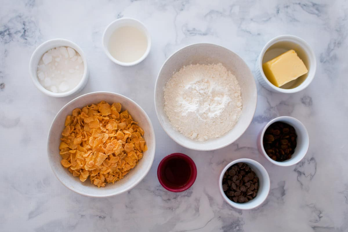 The ingredients for cornflake cookies with sultanas and chocolate chips in individual bowls.