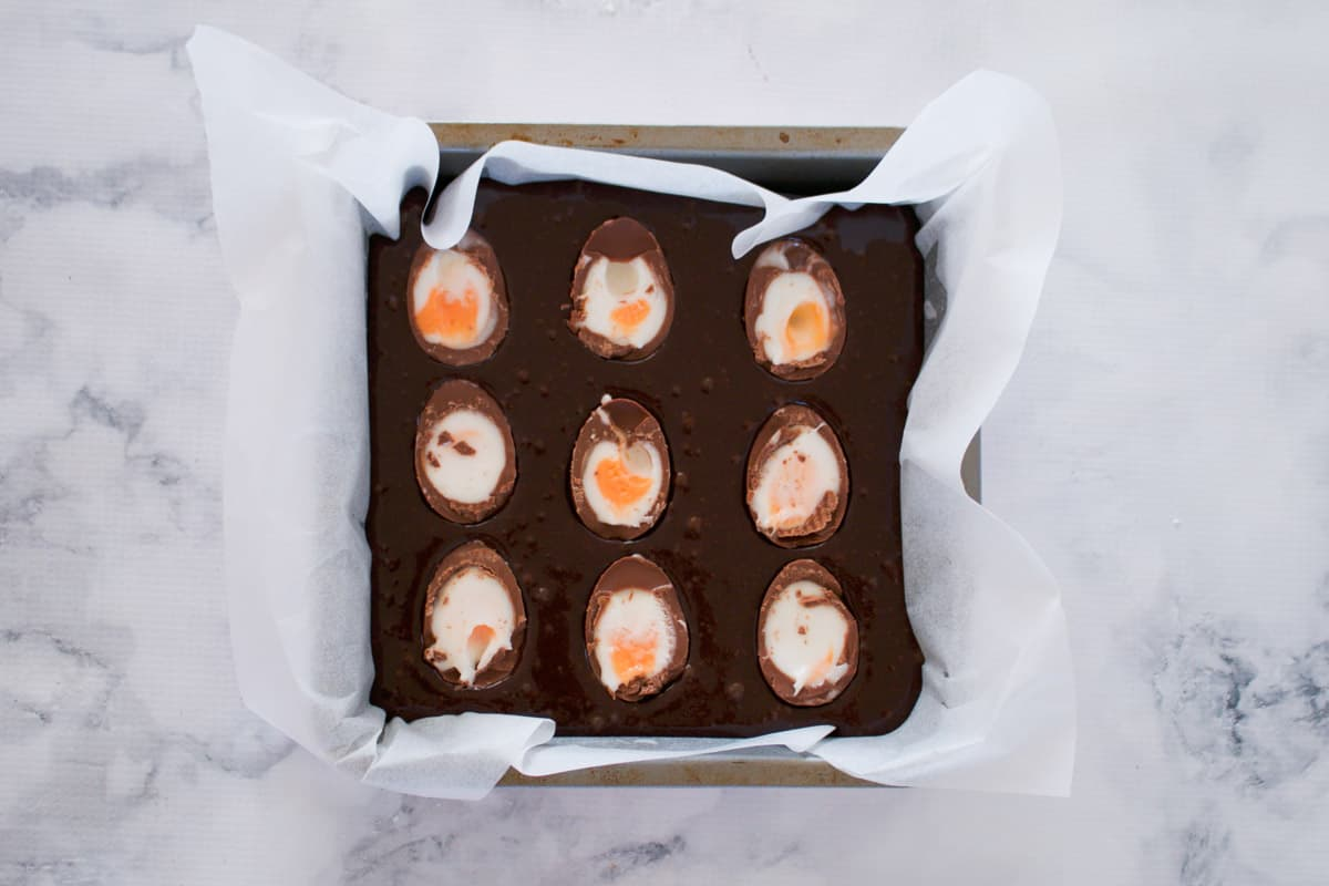 Halved Creme Eggs on top of a brownie slice.