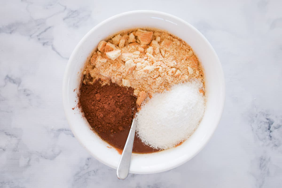 Crushed biscuits, coconut and cocoa in a bowl.