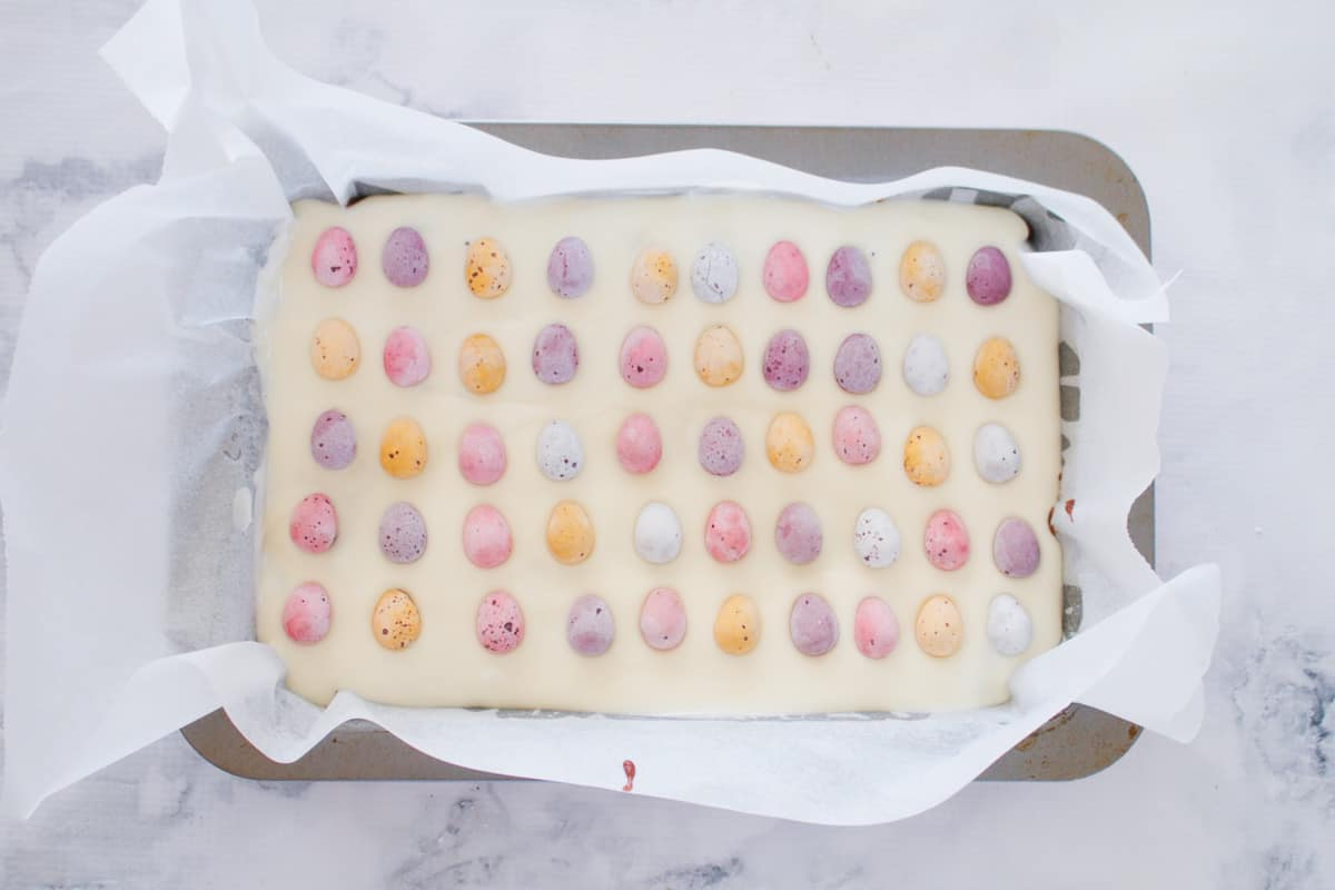 Mini pastel easter eggs on top of a white chocolate slice.