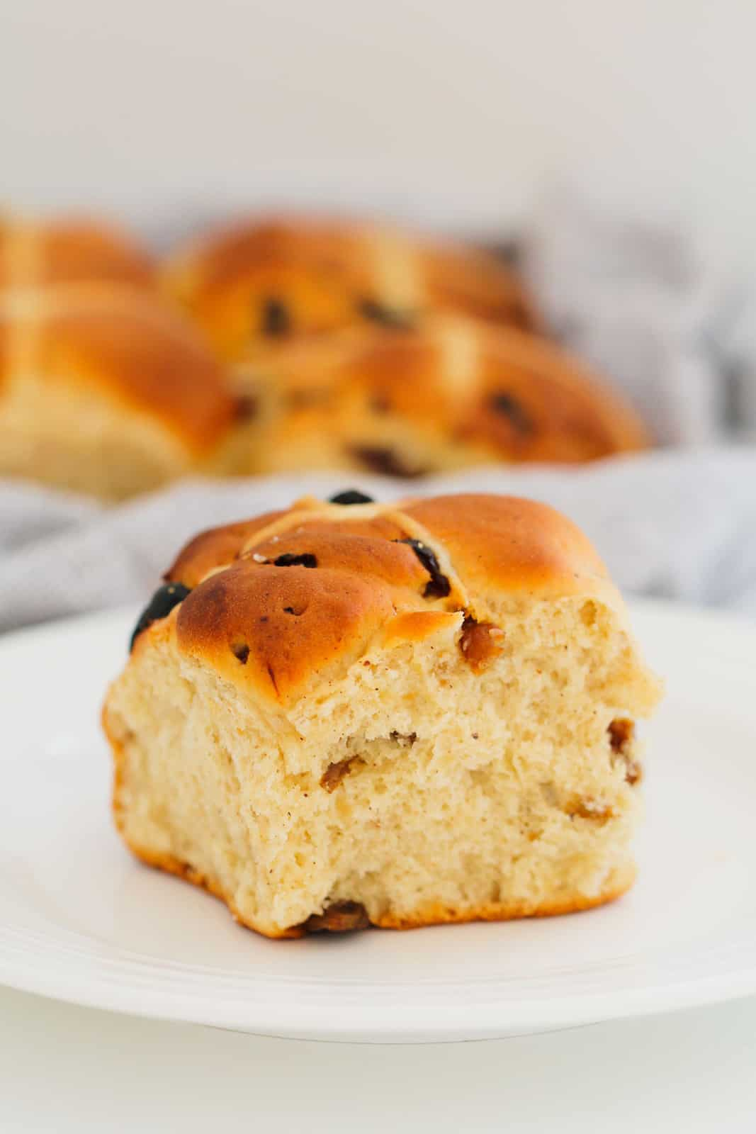 An Easter fruit bun on a plate with more buns in the background.