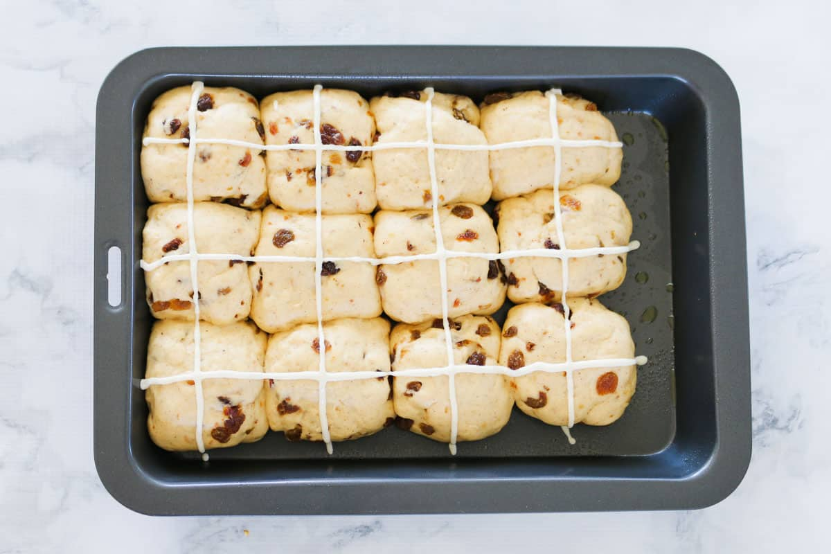 A tray of unbaked fruit buns with crosses piped on top.