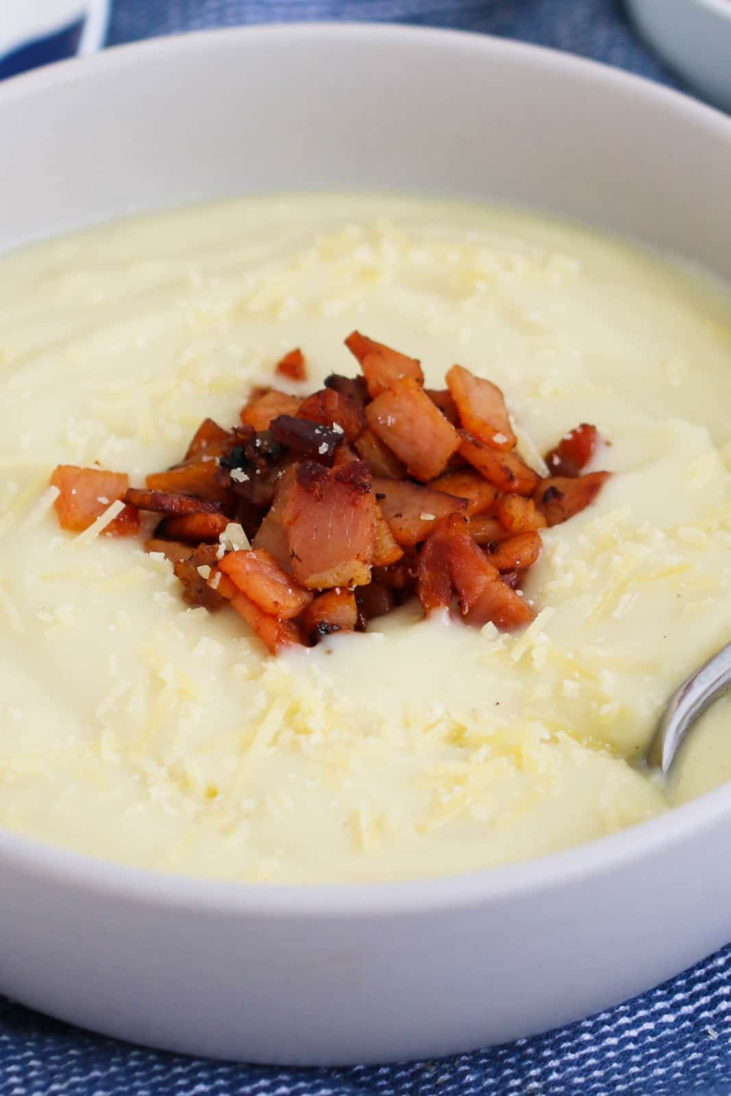 Bacon pieces on top of a bowl filled with creamy white soup.