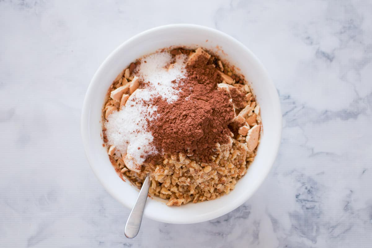 Cocoa, coconut and crushed biscuits in a mixing bowl.