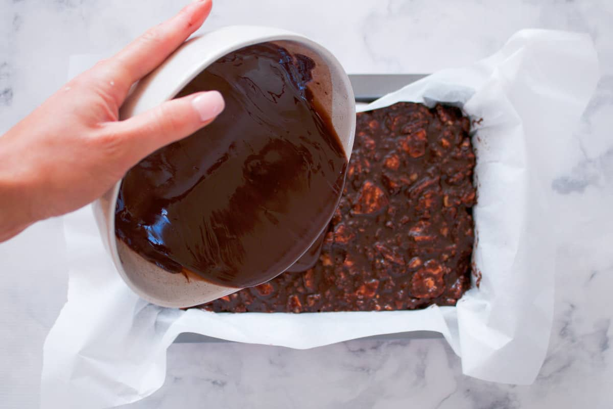 Melted chocolate being poured over a chocolate biscuit slice.