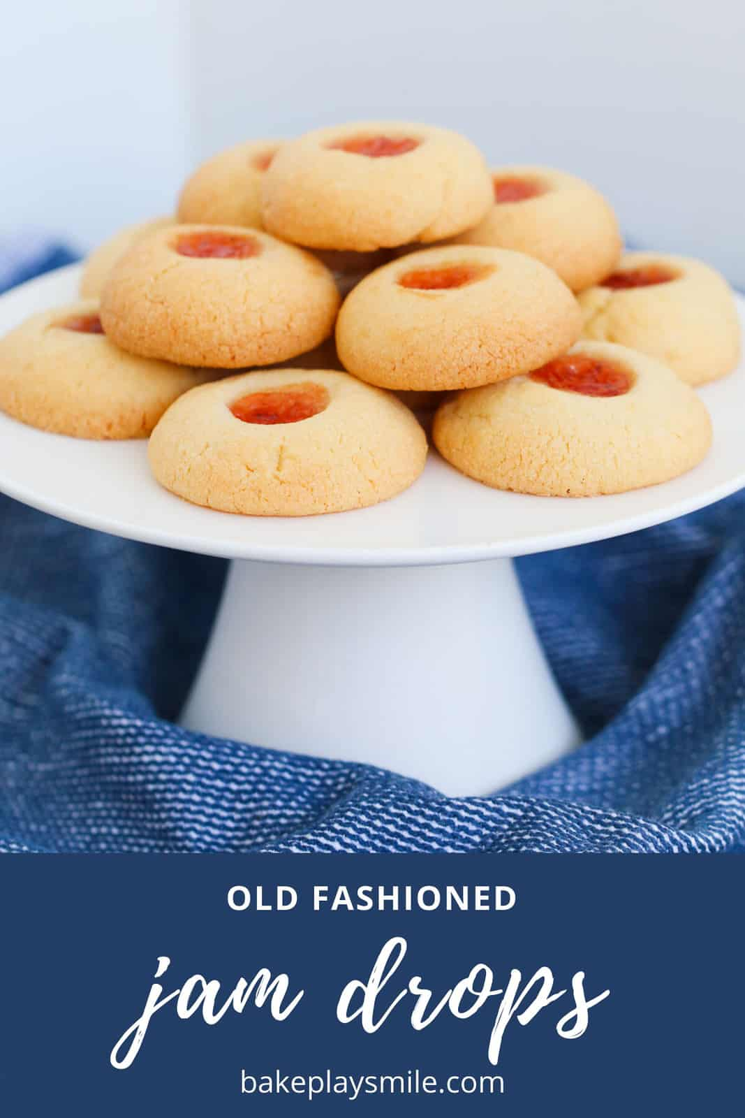 A white cake stand topped with cookies filled with jam.