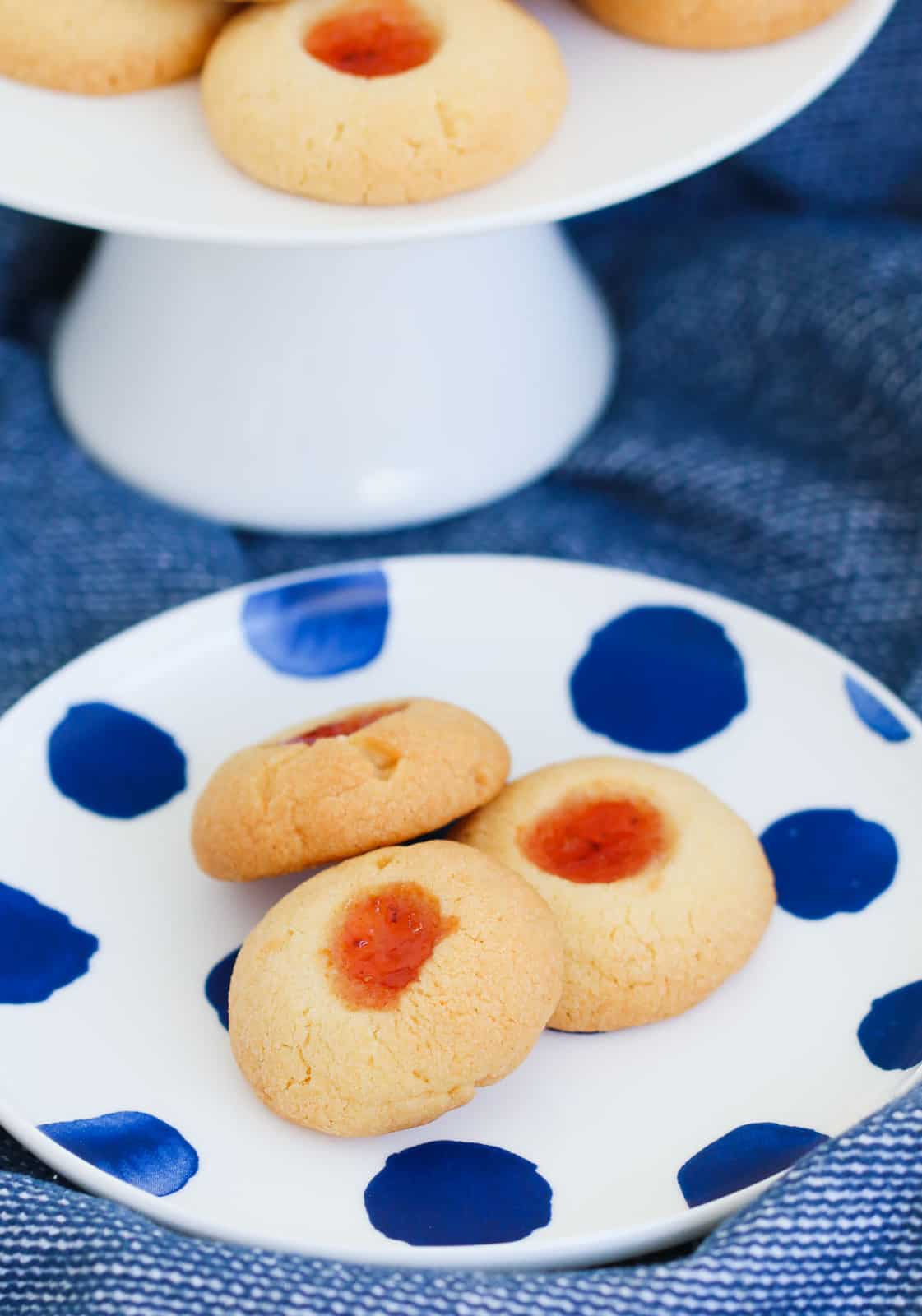 Jam cookies on a blue and white spotted plate.