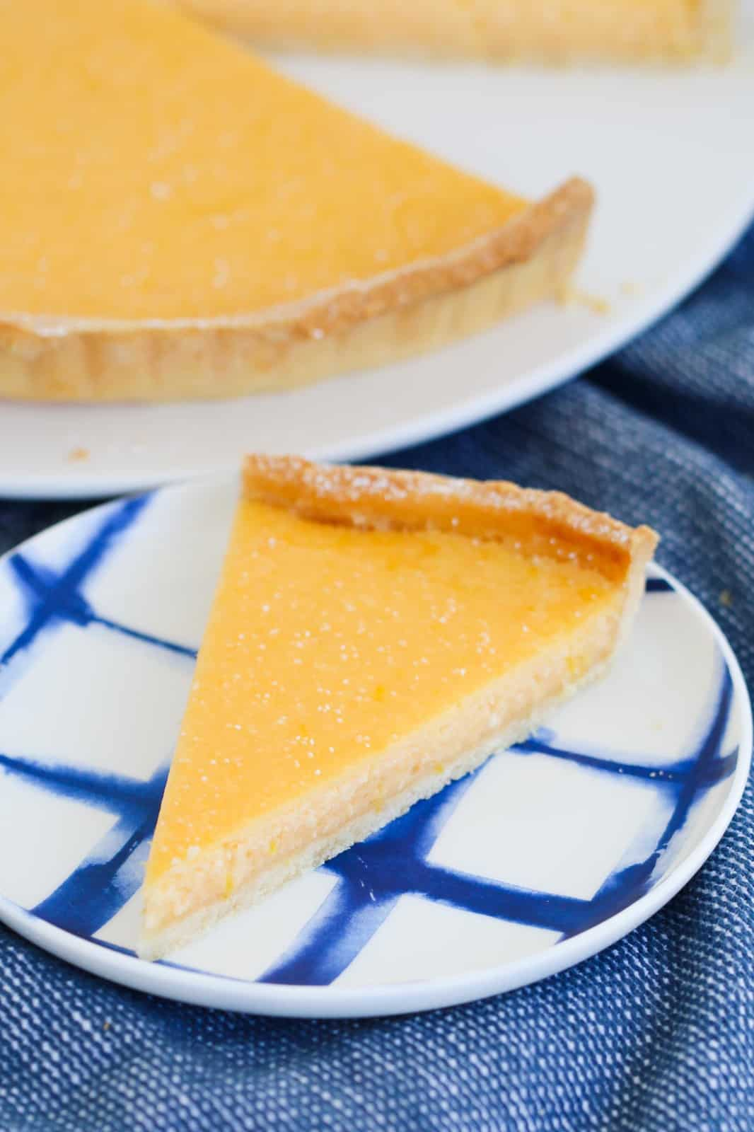 A slice of lemon tart on a blue and white plate.